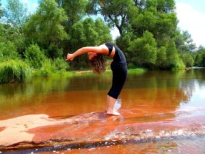 Image of Girl doing Bikram Yoga backbend by lake and trees