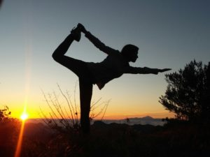 image of woman doing standing bow pulling pose at sunset